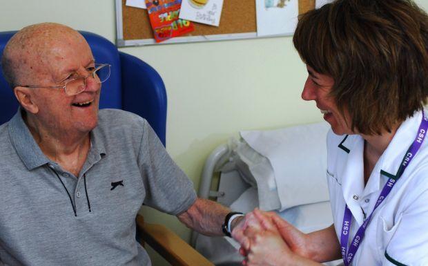 A nurse holding patient's hand